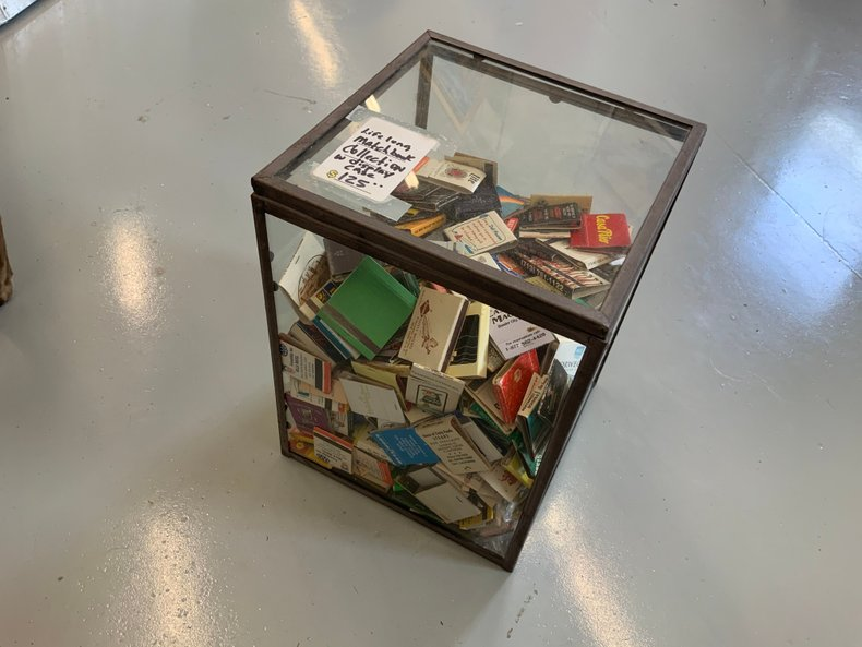 Original old match book collection in glass display cabinet